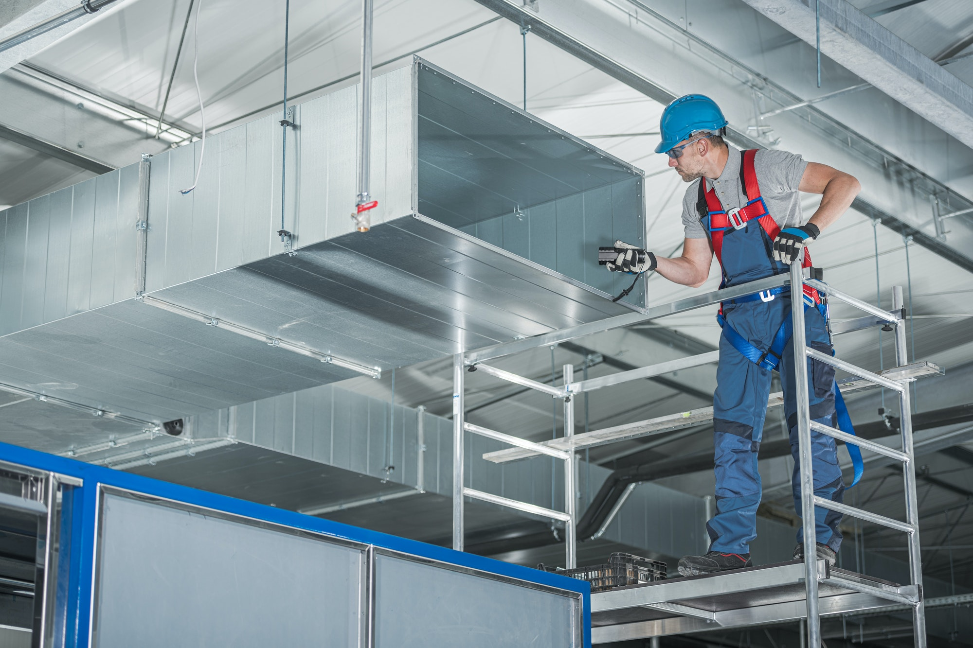 hvac-technician-testing-newly-installed-warehouse-ventilation-system
